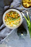 Butter squash pasta salad with zucchini slices, cheddar cheese and scallion stock photo