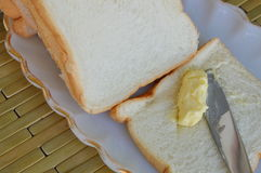 Butter with table knife on bread Royalty Free Stock Photo