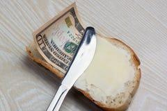 Butter und Geld auf einer Scheibe brot Lizenzfreie Stockfotos