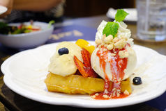 Butter waffle with banana and icecream. Butter waffle with banana,cherry,strawberry and vanilla icecream stock photo