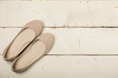 Buttercream women`s shoes ballerinas on wooden background. Selective focus royalty free stock photo