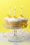 Buttercup Fairy Cakes. Glass comport of buttercup fairy sponge cakes with lit candles Stock Photography