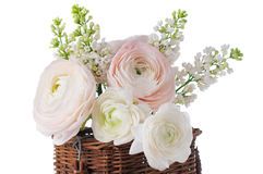 Buttercups and white lilac in a wicker basket Stock Photo