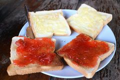Buttered bread and strawberry jam on tableware royalty free stock photo
