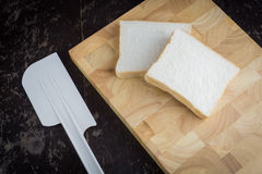 Buttered bread on a wood cutting board. Buttered and bread on a wood cutting board Royalty Free Stock Images