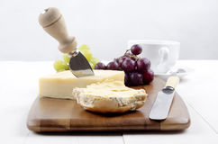 Buttered bun and irish cheddar cheese. Irish cheddar cheese with a cheese knife, half of buttered bun, cup of coffee and grapes on wooden board Royalty Free Stock Photos