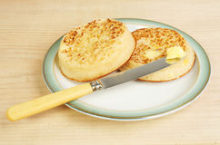Buttered crumpets. On a plate with a knife on an old wooden surface Royalty Free Stock Photography