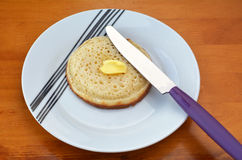 Buttered English crumpet with knife Royalty Free Stock Images