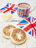 Buttered English crumpets with cup of tea and flag in closeup Stock Photo