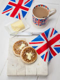 Buttered English crumpets with cup of tea and union jacks Stock Image