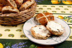 Buttered Hot Cross Buns. Hot Cross Buns buttered set on a tablecloth. Pastry is spiced English bun with currants or raisins and is associated with Good Friday Royalty Free Stock Photos