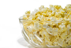 Buttered Popcorn. A glass bowl full of fresh buttered popcorn isolated on white background stock image