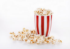 Buttered popcorn in a striped bowl over white background Royalty Free Stock Images