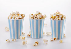 Buttered popcorn in striped paper cups over white background. Buttered popcorn in vintage striped blue-white paper cups over white background Royalty Free Stock Photo