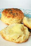 Buttered scone. Two scones, one cut and buttered, on an elegant tea plate Stock Images