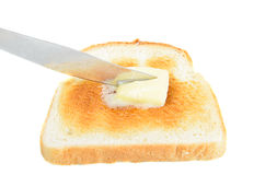 Buttered Toast. A slice of toast being buttered with a knife, isolated on white Stock Images