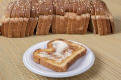 Buttered Toast With Defocused Loaf In Background Stock Image