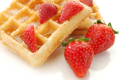 Buttered waffle with strawberries. Buttered Belgium waffles with fresh strawberries on white Royalty Free Stock Photography