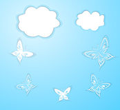 Butterflies and clouds from paper on a blue background Royalty Free Stock Photo