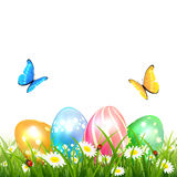 Butterflies flying over colored Easter eggs on grass Stock Images