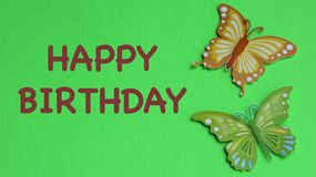 Butterflies on a green background. Two colorful butterflies laying flat on a green background with happy birthday in brown text stock images