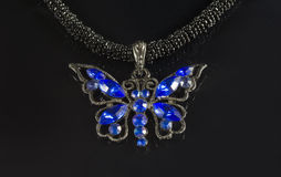 Butterfly. Piece of jewelry with blue gems in the form of a butterfly on a black background royalty free stock image