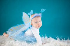 Butterfly baby. Cute baby girl on blue background Stock Photos