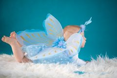 Butterfly baby. Cute baby girl on blue background Royalty Free Stock Photo