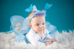 Butterfly baby. Cute baby girl on blue background Royalty Free Stock Photography