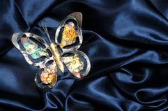 Butterfly on blue satin Stock Photo