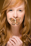 Butterfly covering woman's mouth Royalty Free Stock Photos