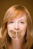 Butterfly covering woman's mouth Stock Image