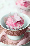 Butterfly cupcake. Embossed butterfly cupcake in an old fashioned teacup stock photo