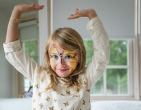 The Butterfly Effect. A Young Girl Showing Off a Butterfly Painted on her Face Royalty Free Stock Image