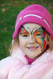 Butterfly Face Painting. A pretty four-year-old girl shows off her butterfly face painting and faux fur coat stock image