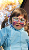 Butterfly Face Painting on Pretty Girl. A three-old girl with beautiful brown eyes plays in a treehouse at a birthday party with elaborate butterfly face royalty free stock photography
