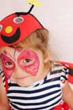 Butterfly Face Painting. A pretty three-year-old girl shows off her butterfly face painting royalty free stock photo