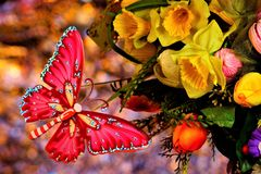 Butterfly flies on a bouquet of flowers on a festive rainbow background bokeh.  The butterfly symbolizes transformation and beauty. On a summer background royalty free stock photography