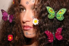 Butterfly Girl. Girl wearing makeup made of rhinestone flowers. She has butterflies and daisies in her hair Stock Image