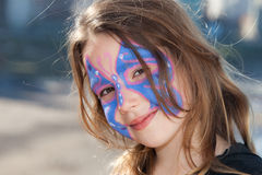 Butterfly girl. Cute little girl with a butterfly face paint stock image