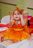 Butterfly girl. Baby girl dressed as butterfly sits on a table with a fork in hand stock image