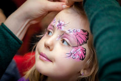 Butterfly girl. Little girl having her face painted into butterfly and flowers royalty free stock photo