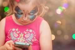 Butterfly girl texting on mobile phone royalty free stock photography