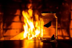 Butterfly in a jar. On the background of a fireplace royalty free stock photos