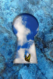 Butterfly on a keyhole. A yellow butterfly sitting on a keyhole Royalty Free Stock Images