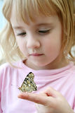 Butterfly and Little Girl. A little girl looks closely at a butterfly that sits on her finger stock photo