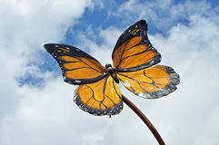 Butterfly model against a cloudy blue sky Royalty Free Stock Photo