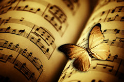 Butterfly and music. Sepia tone image of an open music book and a butterfly flying over it Stock Photos