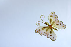 Butterfly ornament. Christmas butterfly decoration, Gold and white. Pale blue background Royalty Free Stock Image
