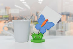 Butterfly Paper note holder and a cup of coffee. On the white table Royalty Free Stock Image